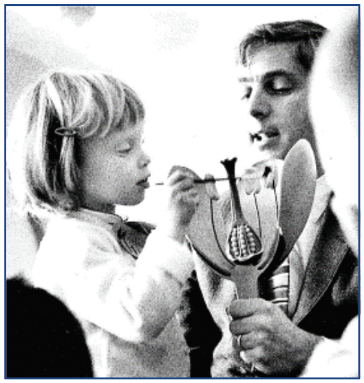 Irwin Slesnick showing flower parts to a child