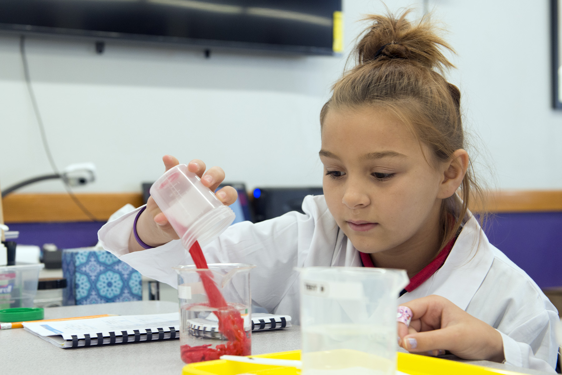 A young girl in a lab coat pouring a red liquid into a beaker