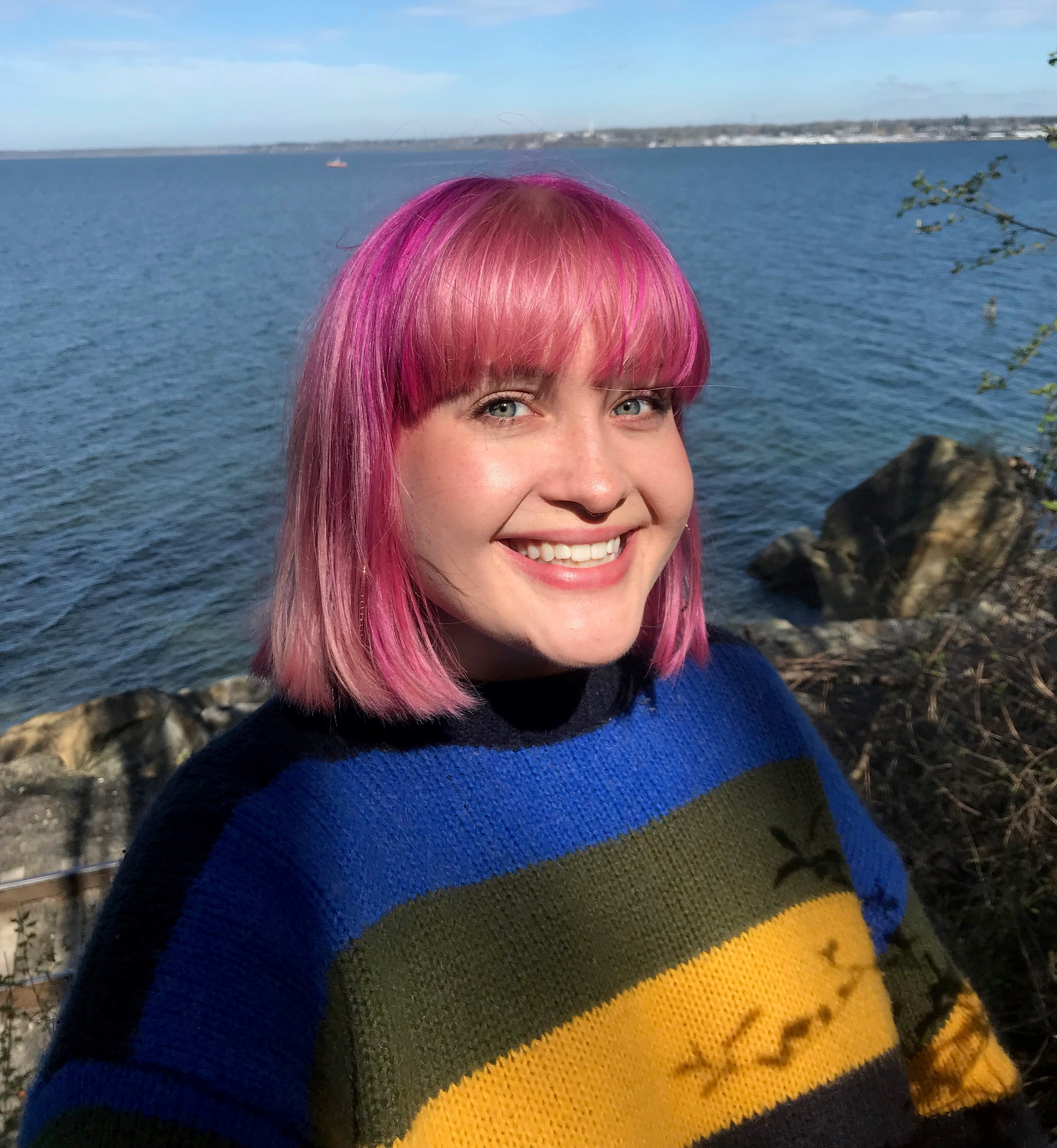 Shannon, with pink hair and wearing a boldy striped sweater, posing in front of a rocky shoreline