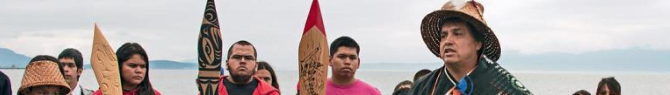 Image of Lummi Nation members at Cherry Point, WA holding canoe paddles